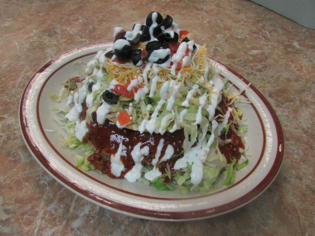 Salad made with shredded lettuce, ground meat, shredded yellow cheese, sliced black olives, diced tomatoes, drizzled in sour cream