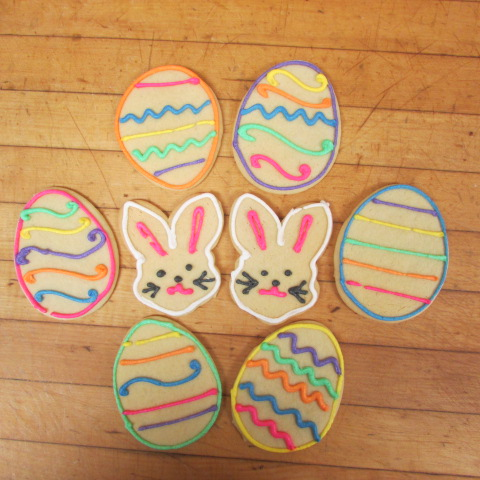 two easter bunny cookies surrounded in decorated egg cookies