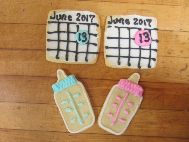 Two cookies that look like baby bottles with pink and blue frosting and two cookies that look like a June Calender with the 13 highlighted in frosting