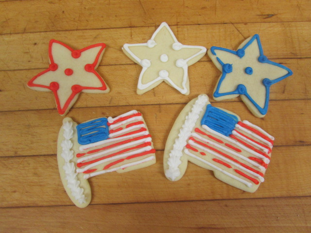 Three re, white and blue star shaped cookies with two cookies that resemble the american flag