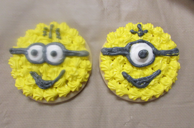 Two yellow frosted caked resembling the minion characters
