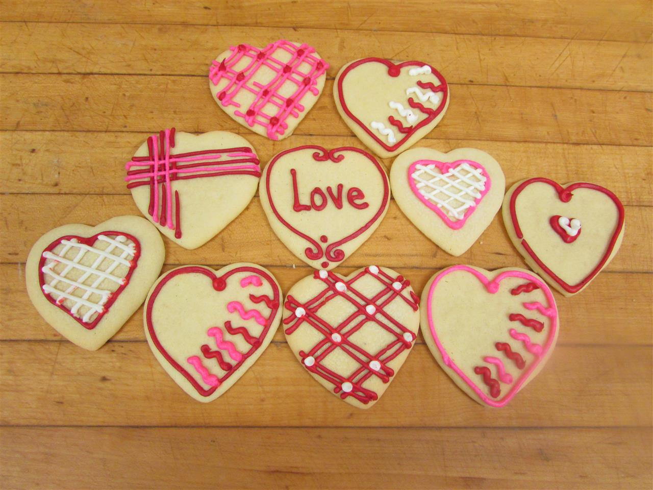 Sugar cookies in the shape of hearts decorated in pink,white and purple frosting