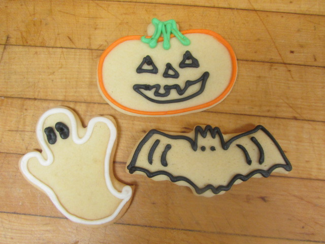 A ghost cookie, a bat cookie and a pumpkin cookie decorated in frosting