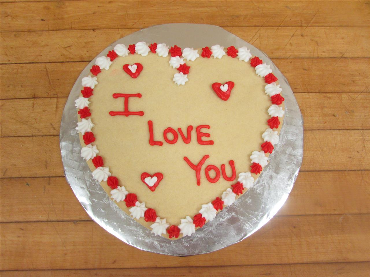 cake in the shape of a heart that sayas i love you in red frosting with a bordering of red and white frosting