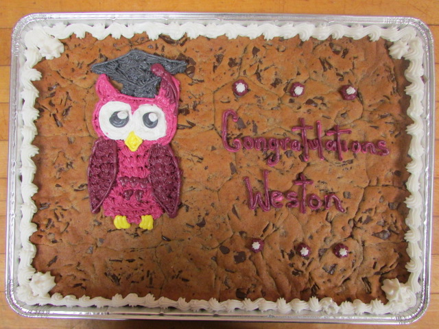 Rectangle cookie cake that says Congratulations Weston on it decorated with a pink owl wearing a graduation cap