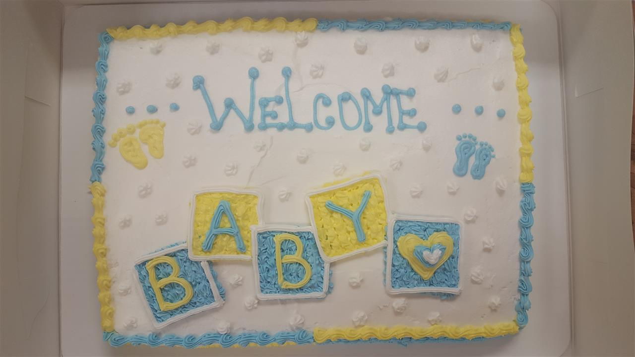 Rectangle cake that says Welcome Baby on it decorated with blue and yellow frosting
