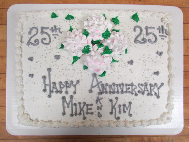 White cake with Happy 25th Anniversary Mike and Kim on it in silver decorated with four light pink flowers in the center