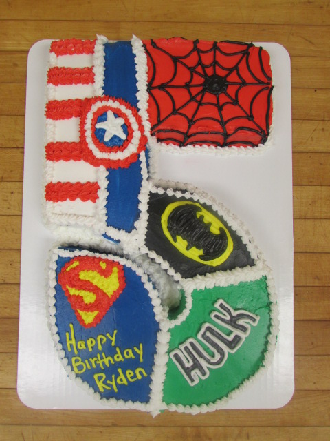 Cake in the shape of a five that is decorated into different sections to represent superman, the hulk, batman, captain america and spider man.