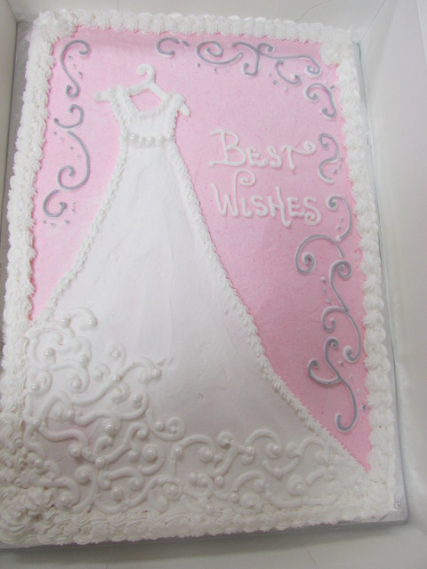"Pink frosted rectangle cake decorated with a hand drawn wedding dress in frosting that reads ""Best Wishes"""
