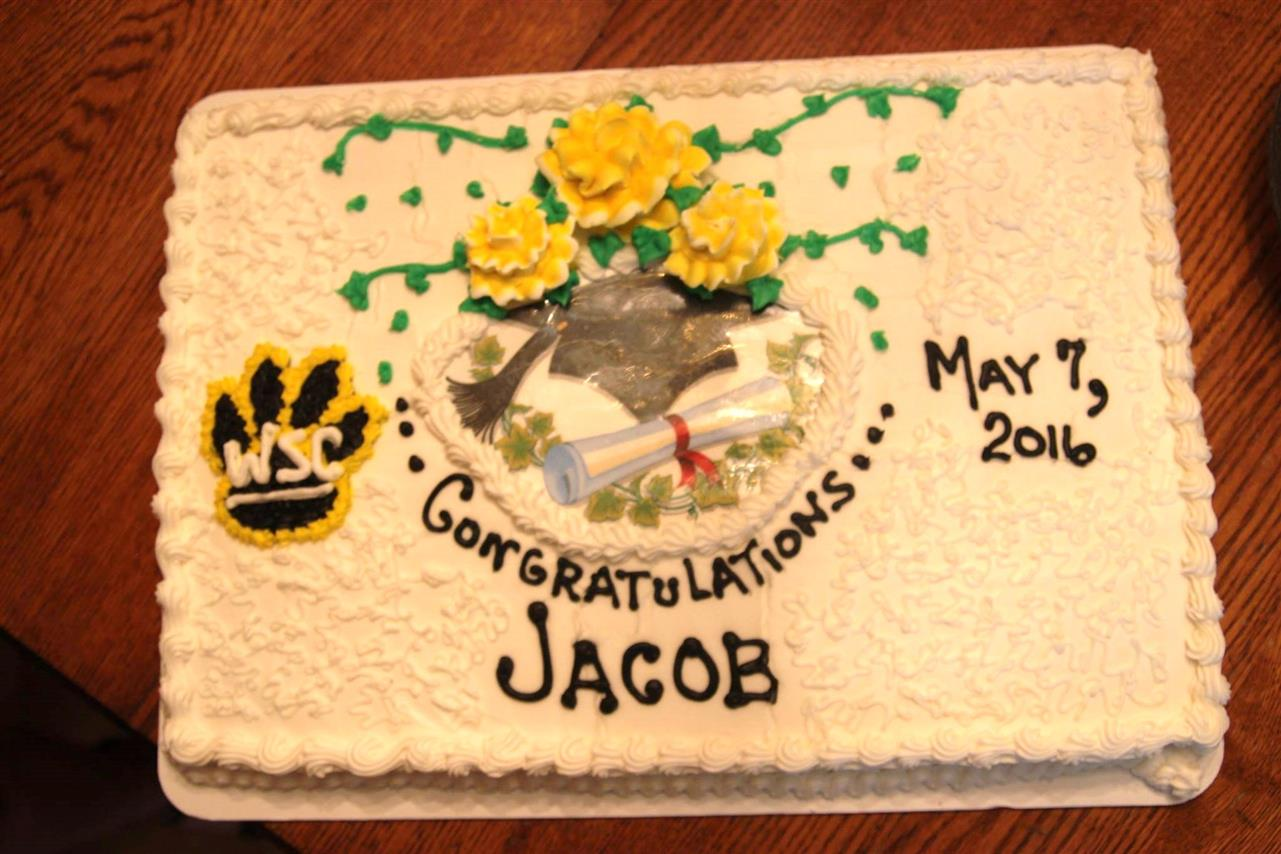 "White frosted cake cake that reads congratulations Jacob May 7th 2016"" decoarted with a paw that reads ""WSC"" and a picture of a diploma in the middle"