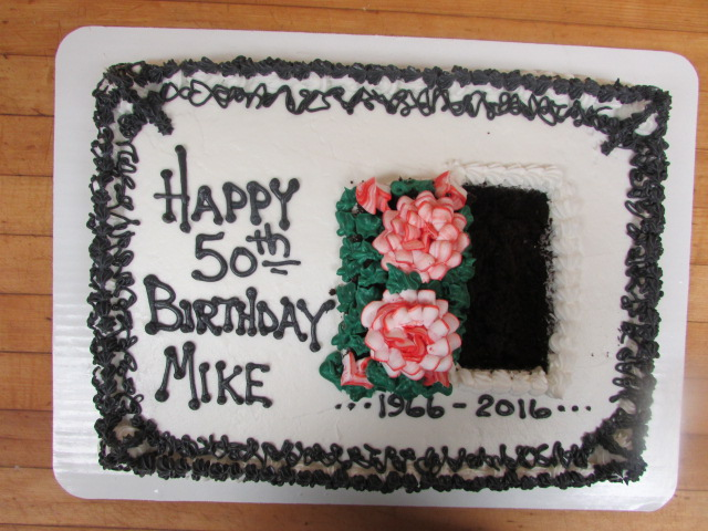 "White square cake that reads ""Happy 50th Birthday Mike 1966-2016"" decorated with frosted flowers and a white squiggly border"