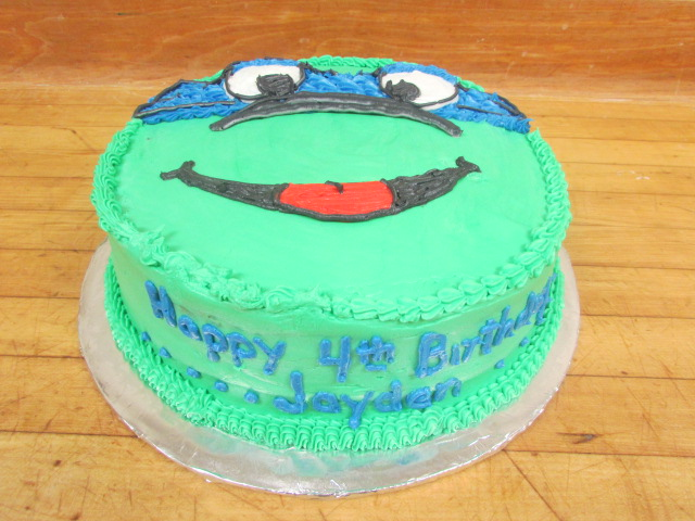 "Teenage Mutant Ninja turtle cake with ""happy 4th birthday Jayden"" frosted on the side"