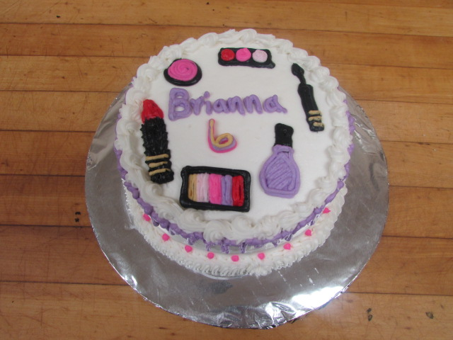 "White frosted cake that reads "" Brianna 6"" decorated with lipstick, eye shadow, nail polish, and a mascara wand made of frosting"