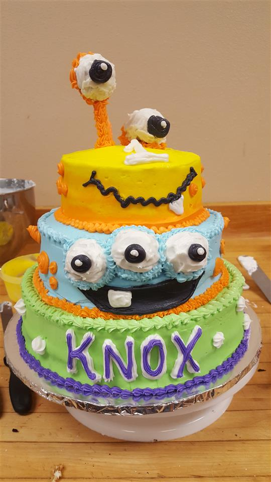 "Three layer green, blue and yellow cake decorated with a different monster at each layer with""Know"" written on the bottom layer"