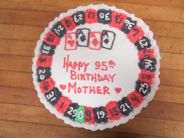 "Poker themed cake decorated like a roulette wheel readin ""Happy 95th Birthday Mother"""