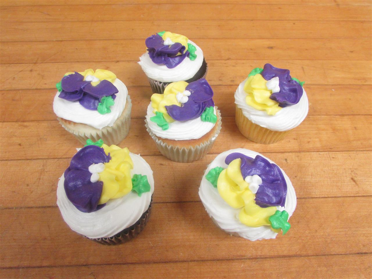 Six frosted cupcaked decorated with yellow and purple flowers made of frosting