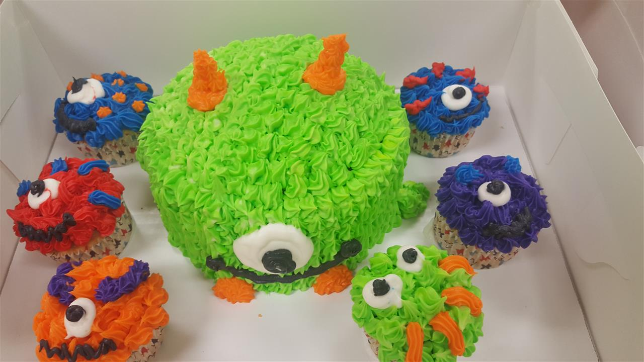 frosted cake resembling a green and orange monster with one eye surrounded by cupcakes that are frosted to resemble various monsters