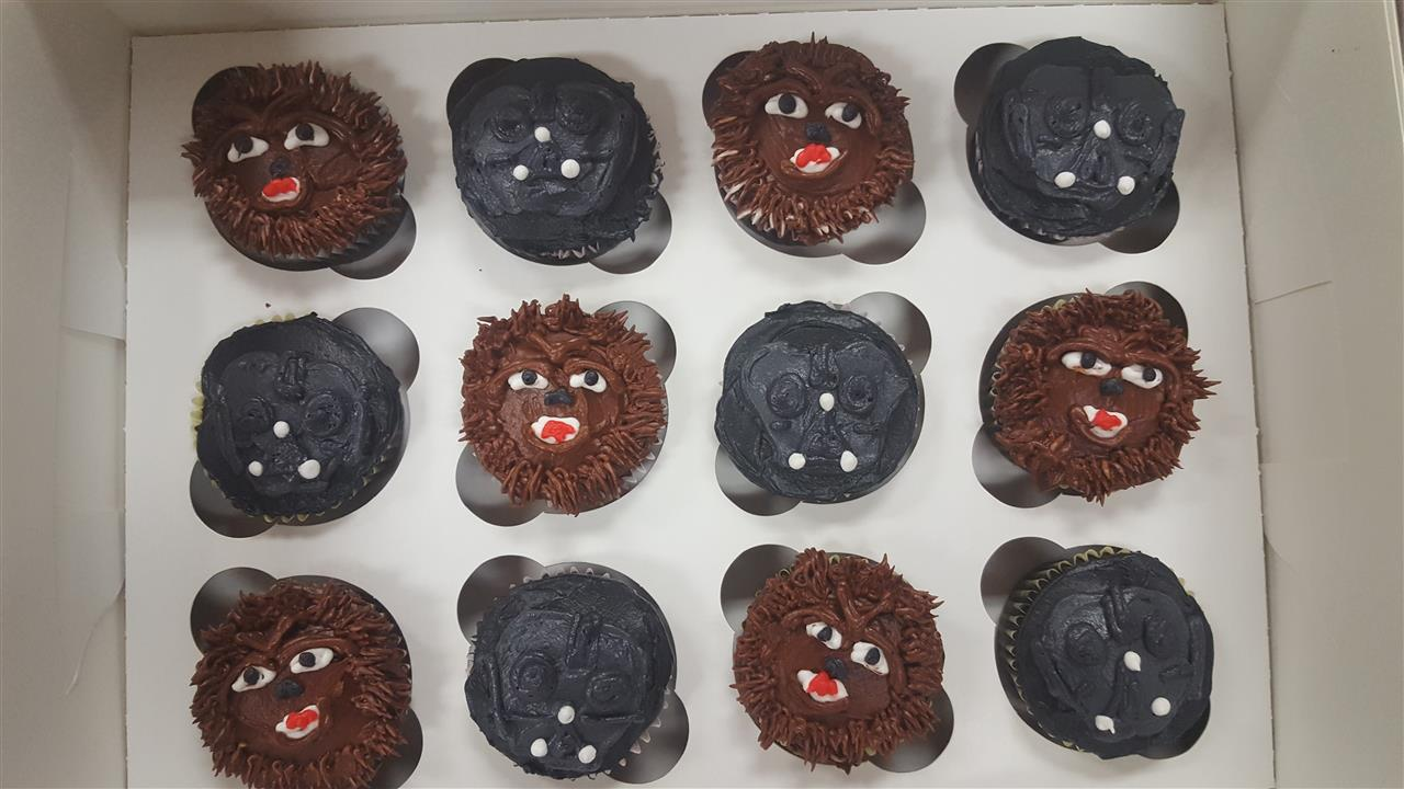 Frosted cup cakes resembling wookie and Darth Vader from star wars