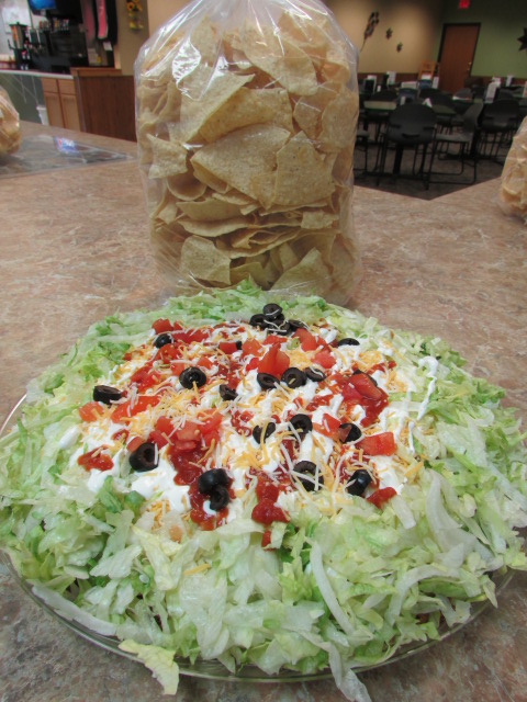 Plate of shredded lettuce toped with sour cream, salasa, diced tomatoes, sliced black olives and a bag og tortilla chips