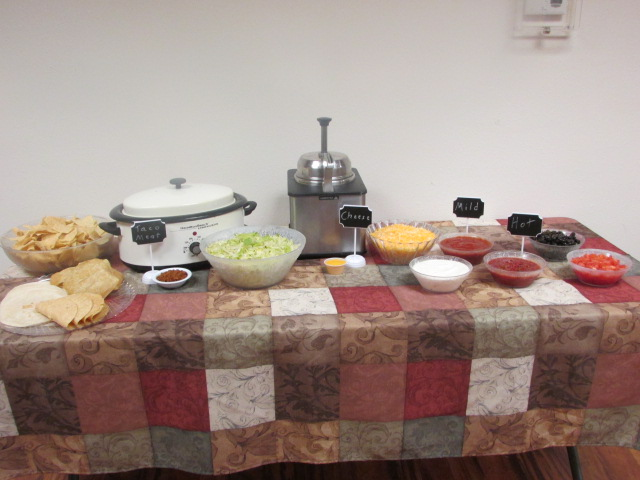 Table with a patterned table cloth set with bowls of taco meat, shredded cheese, shredded lettuce, mild salsa, hot salsa, taco shells and a slow cooker.