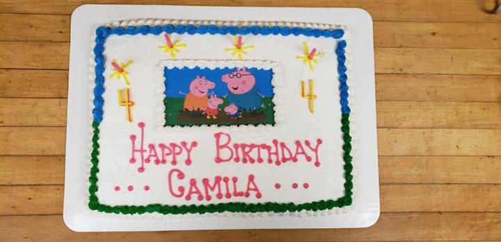 Rectangle cookie that sayas Happy Birthday Camila decorated with cartoon pig characters in the center