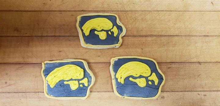 Three cookies frosted with blue and yellow frosting