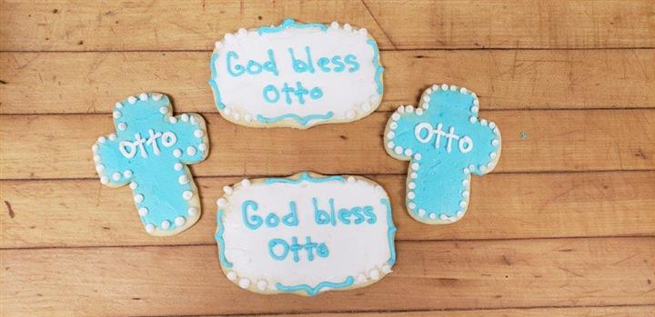 Four cookies in the shape of crosses and squares that say god bless otto