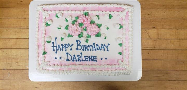 Rectangle cake decorated with pink and white frosted flowers that says Happy Birthday Darlene