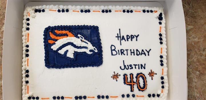 Blue and Orange decorated rectangle cake that says Happy Birthday Justin