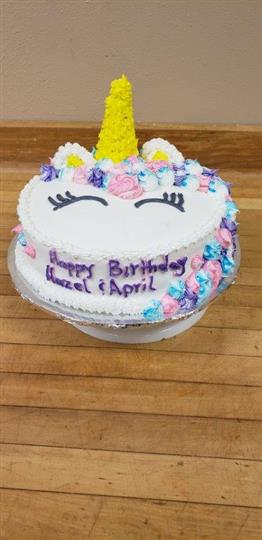 circular cake decorated as a unicorn that says happy Birthday hazel and April