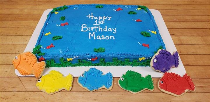A blue rectangle cake that is decorated like an ocean that sayas Happy 1st Birthday Mason with three fish shaped cookies next to it