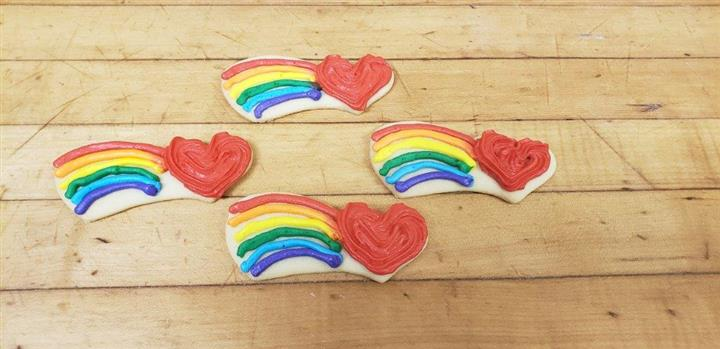 Cookies decorated and shaped like hearts with rainbows