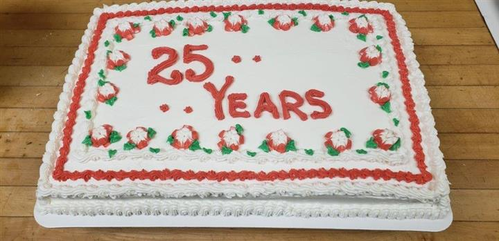 Rectangle cake that says 25 years  with a border of red and white frosted flowers