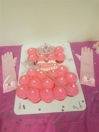 pink cupcakes lined up to look like a dress with a tiara and wand on top and pink silk gloves by the side