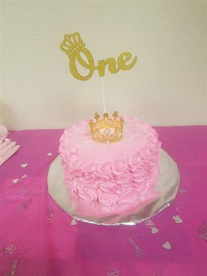 "Pink frosted cake with a gold crown on top a a gold decoration that says ""One"" on it"