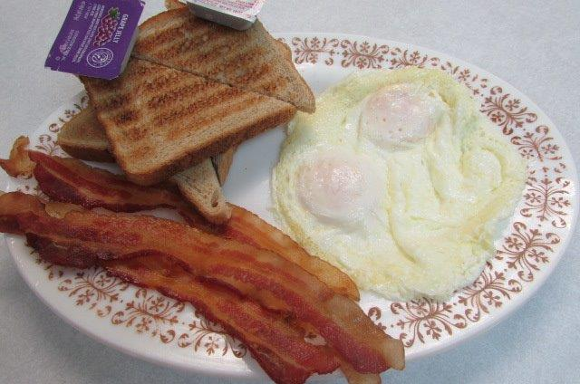 Plate with sunnyside up eggs and three pieces of bacon with a side of toast and grape jelly