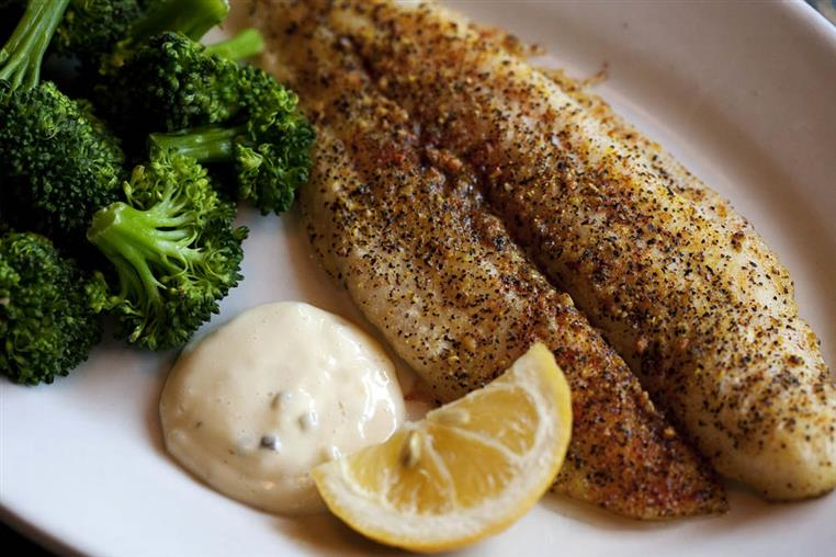 Fish entree cooked on a plate with a small side of broccoli, a lemon wedge and a white creamy sauce.
