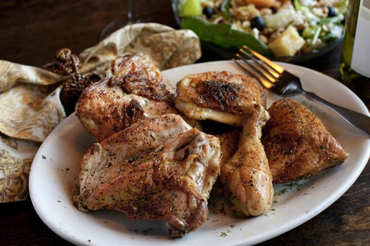 Grilled chicken breasts and drumsticks on a plate.