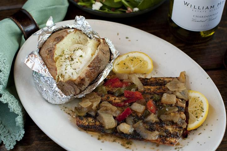 An 8 oz. filet, lightly seasoned in a vinaigrette dressing & char-grilled, then covered in sweet onions & bell peppers with a side baked potato.