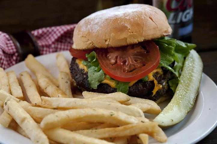 Cheeseburger with lettuce and tomato with a side pickle and french fries,