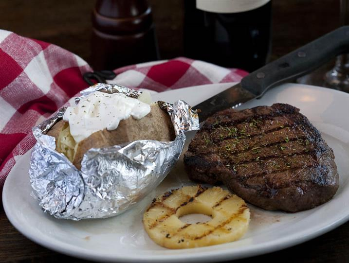 Steak on a plate with a baked potato on the side that is topped with sour cream.