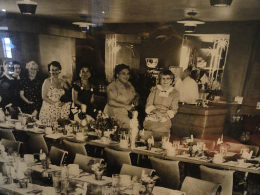 Old black and white image with five women standing in the dining area