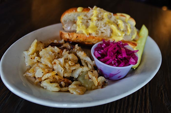 hot dog with mustard, cabbage and potatoes