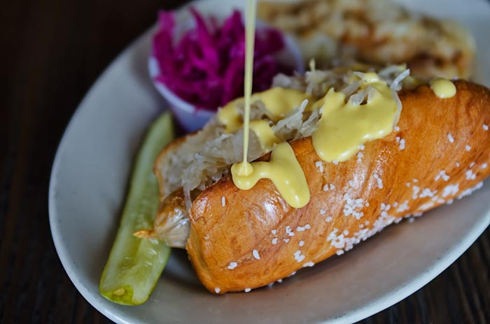 hot dog on a bun with pickle, cabbage and fries