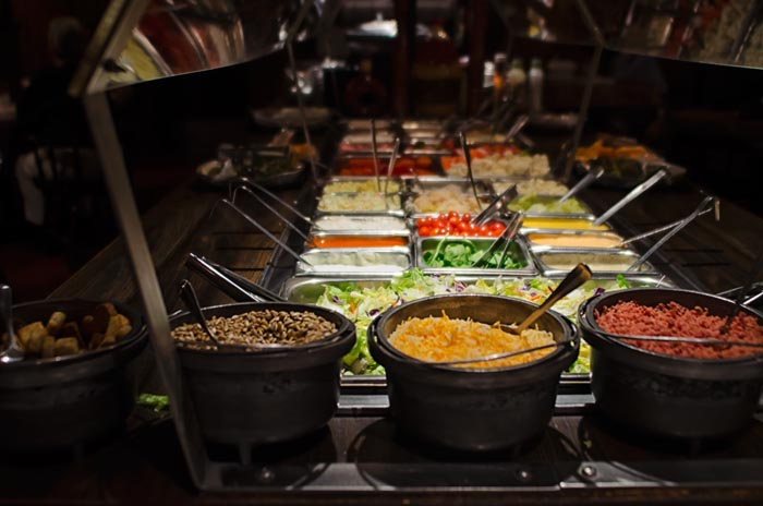 salad bar buffet with various metal trays set up