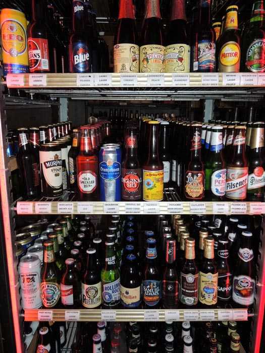 stocked bar fridge with various bottled beers