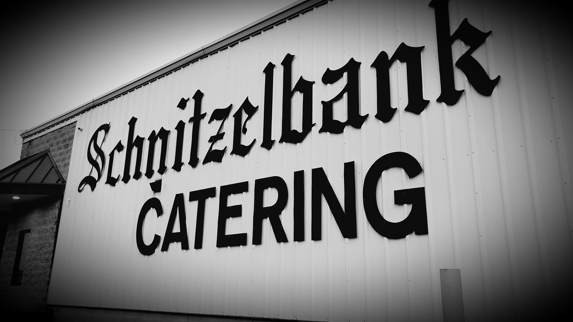 "large sign on sign of building that reads, ""Schnitzelbank Catering"""