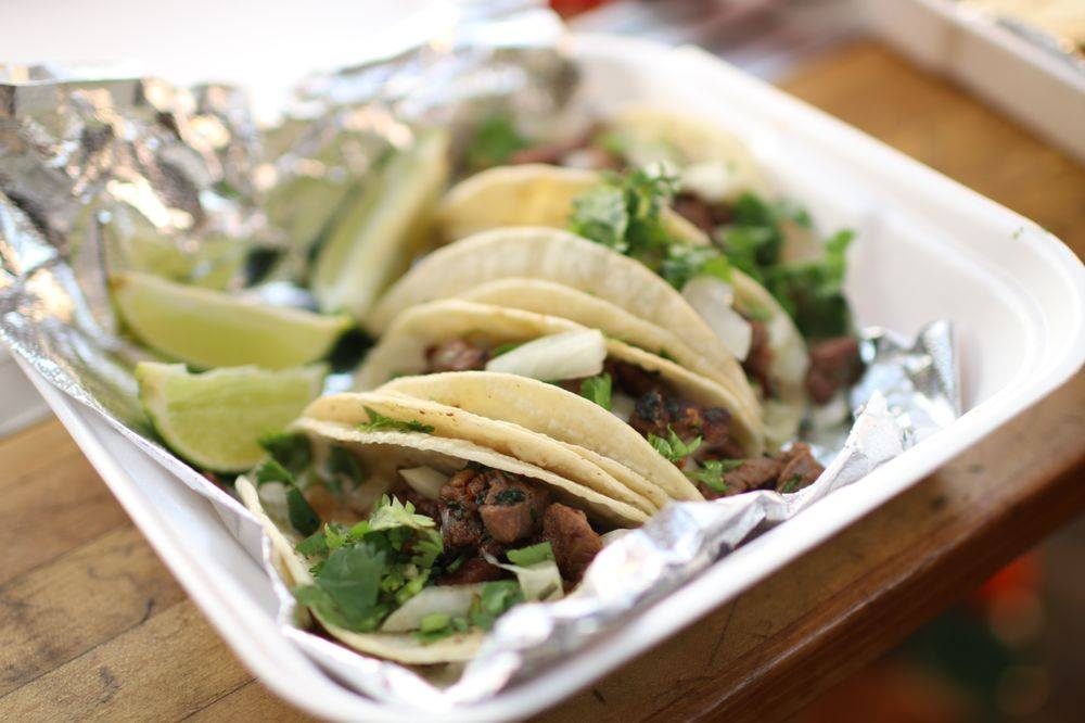 Tacos with beef and lime wedges.