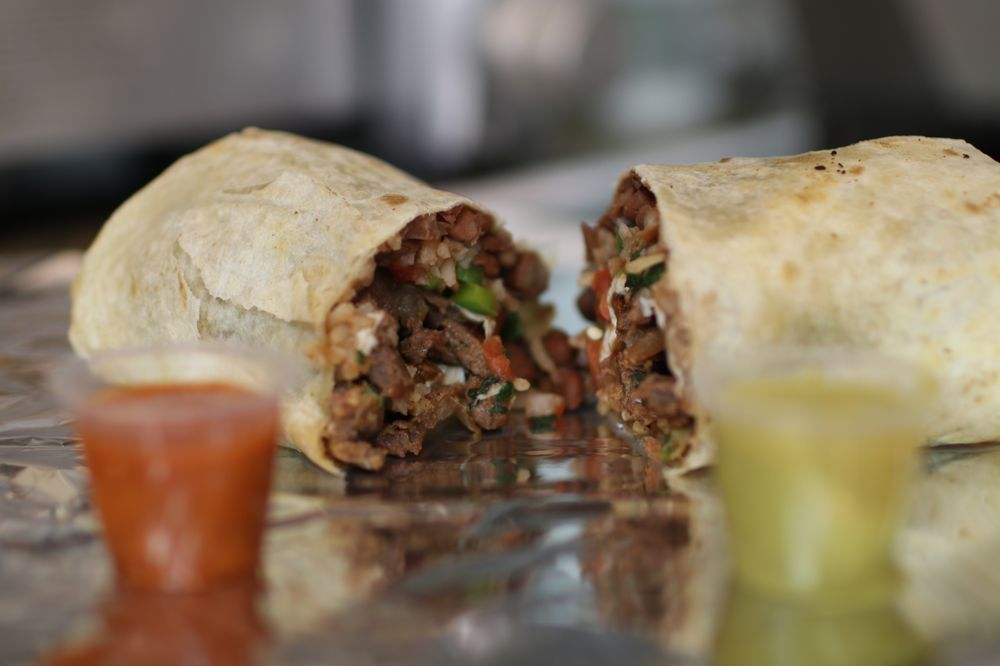 Burrito cut in half with beef and a variety of fillings.