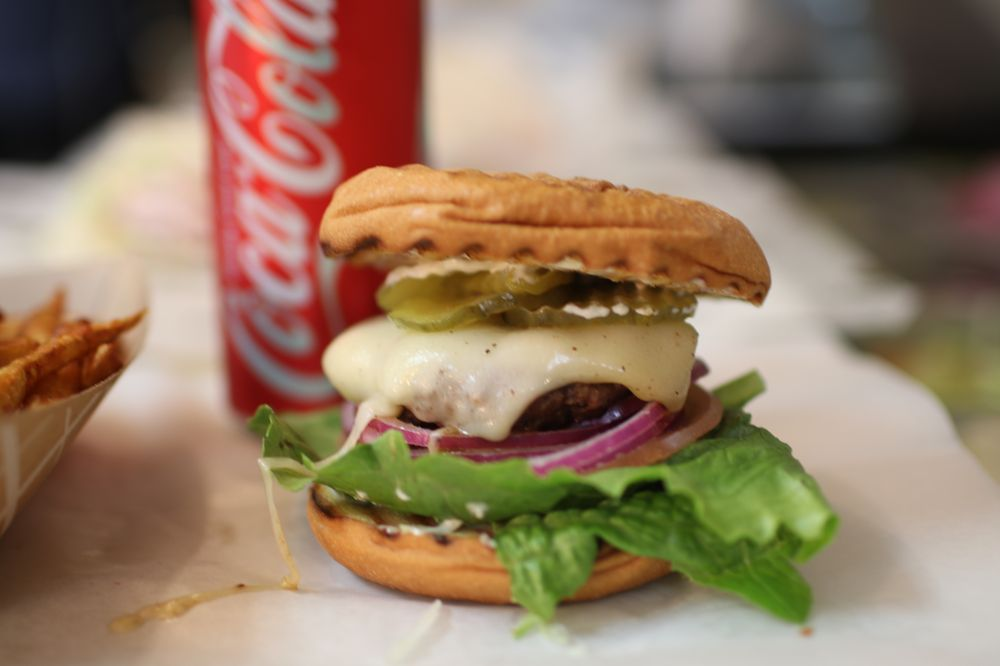 Burger with white melted cheese, lettuce, red onion and sliced pickles. Served with a can of Coca Cola.